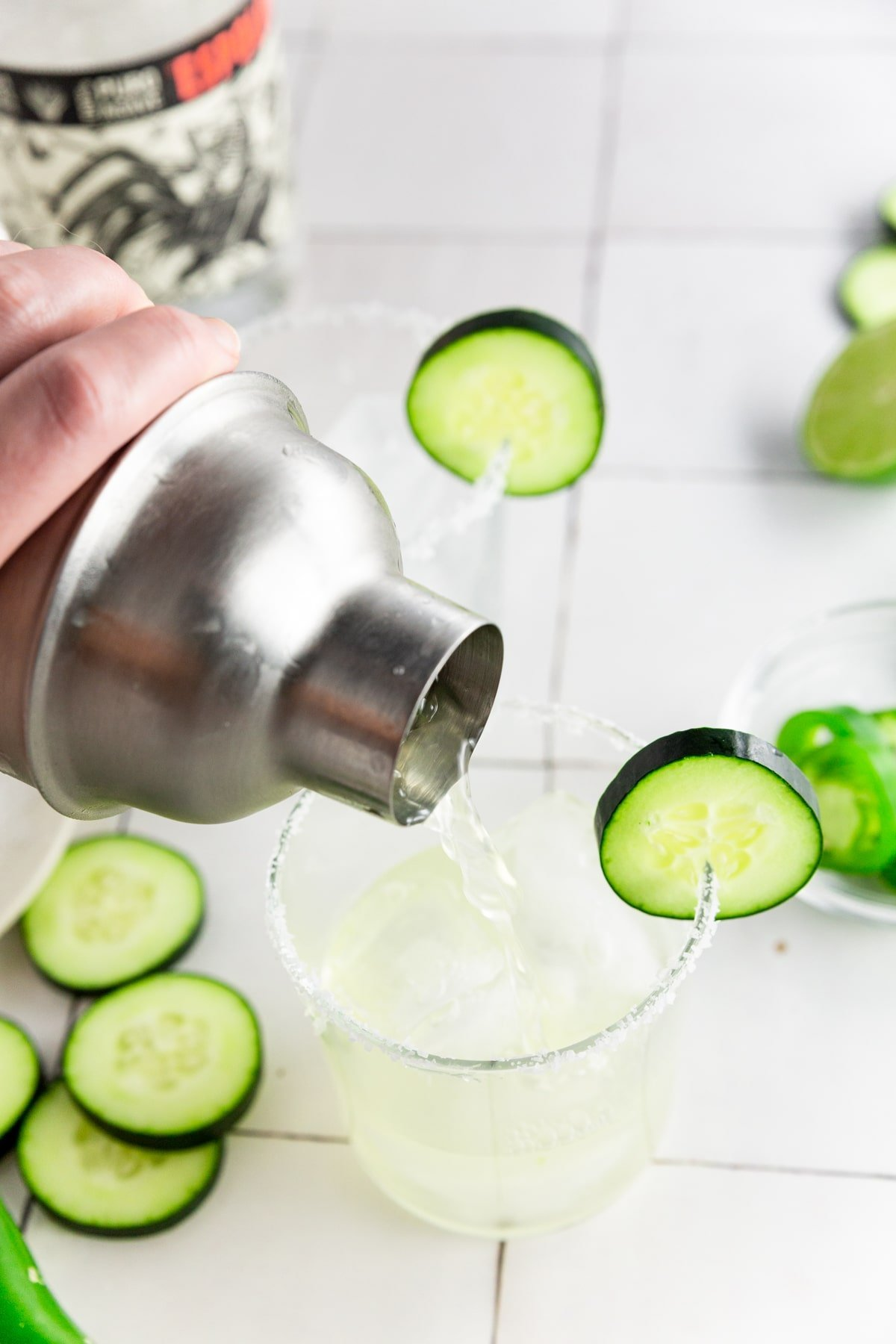 A photo of a cocktail shaker pouring cucumber jalapeño margarita into a glass rimmed with lime juice and kosher salt.