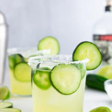 A photo of a cucumber jalapeño margarita with a salted rim and a bottle of tequila and a cocktail shaker in the background.