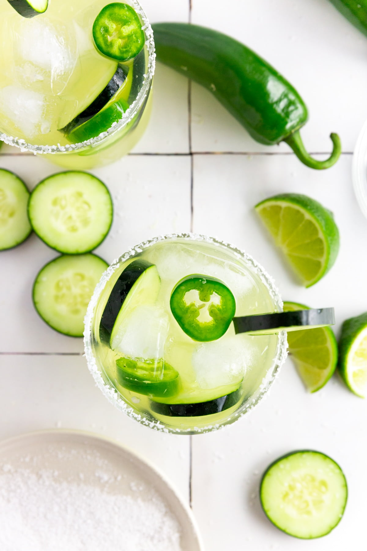 An overhead photo of two margarita glasses filled with jalapeño cucumber margaritas with sliced jalapeño and cucumbers in it and lime wedges on a table.