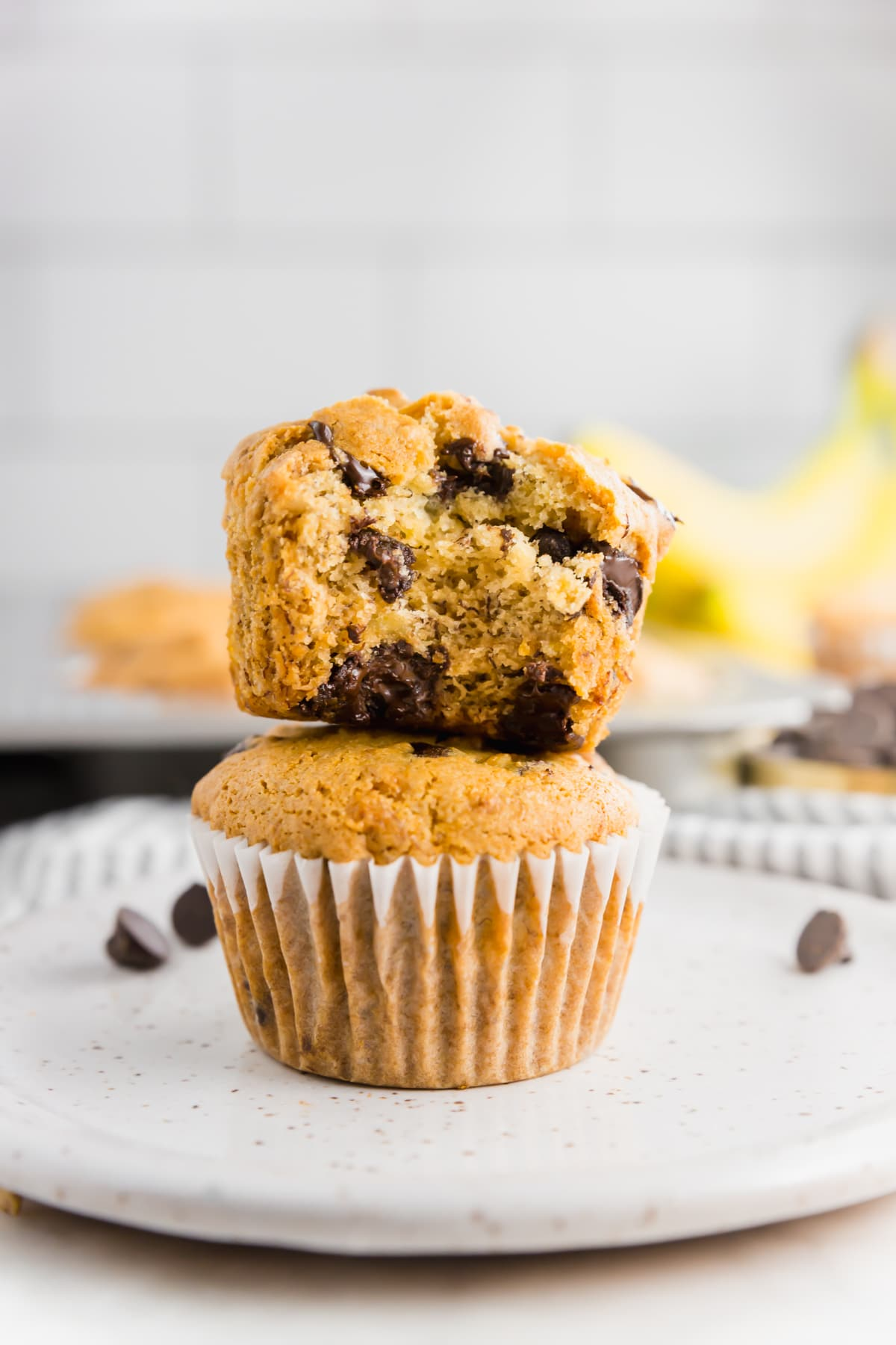 Two gluten-free vegan banana chocolate chips banana muffins stacked on top of each other.