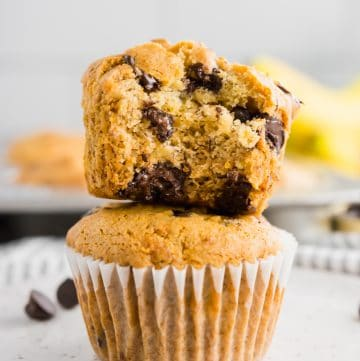 A stack of two banana chocolate chip muffins with the top one cut in half.
