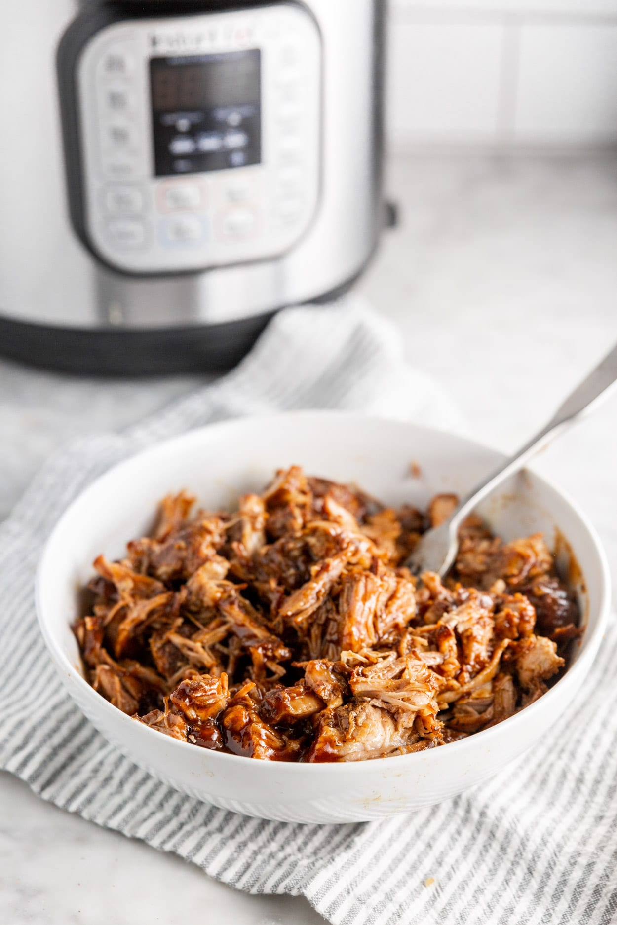 A bowl of shredded BBQ pulled pork in a bowl with an Instant Pot in the background.