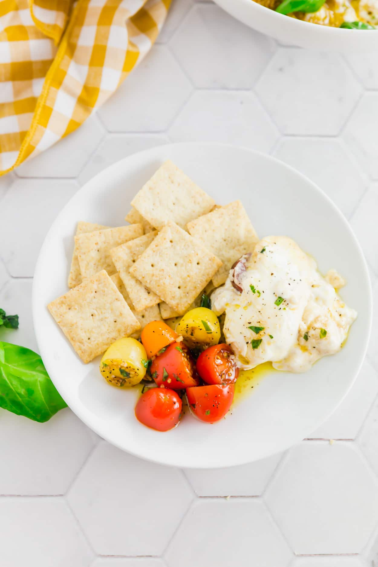 An overhead photo of a plate with gluten-free crackers served with marinated tomatoes and creamy burrata.