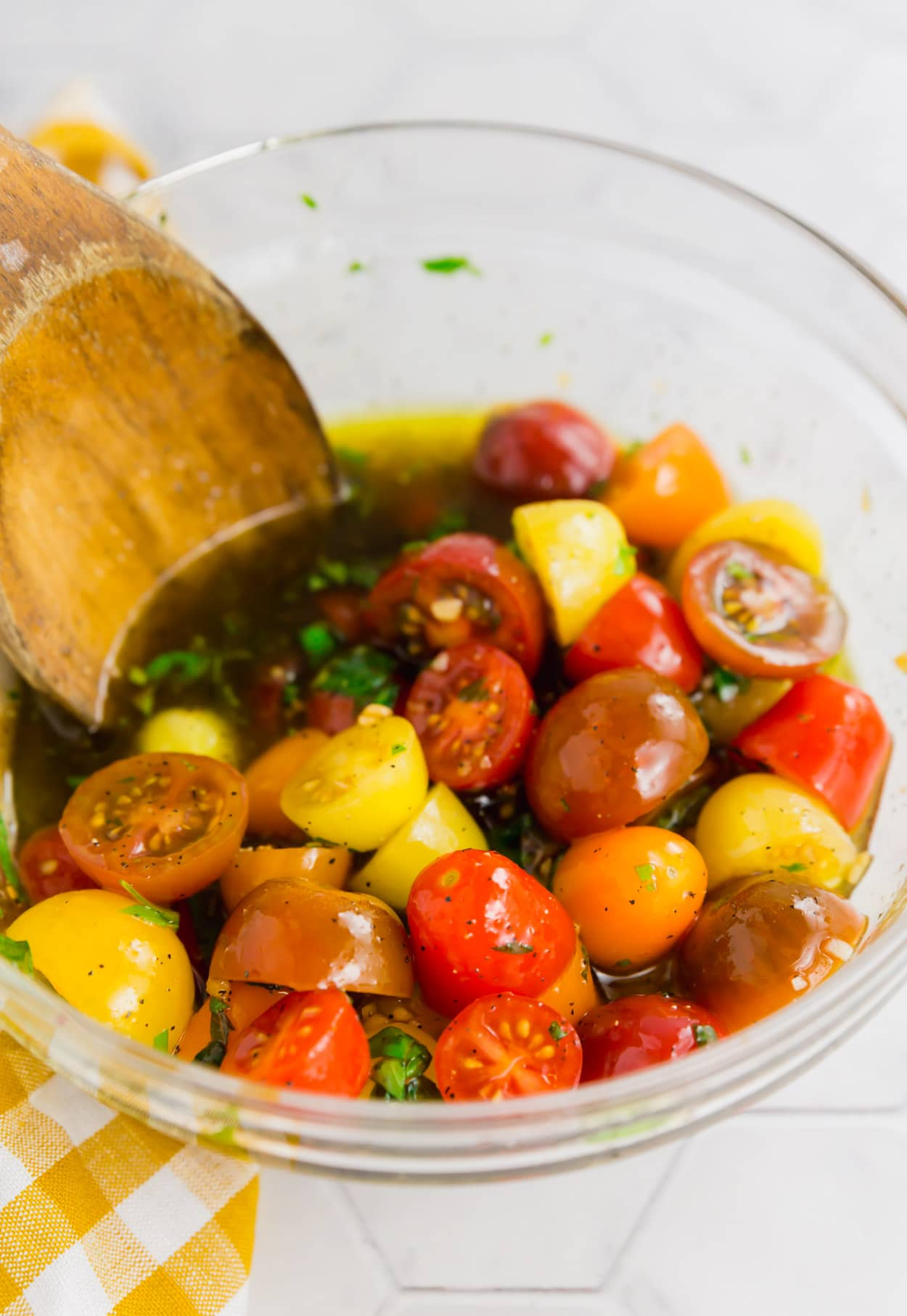A photo of a mixing bowl with colorful cherry tomatoes, olive oil, balsamic vinegar and fresh basil ready to be mixed.