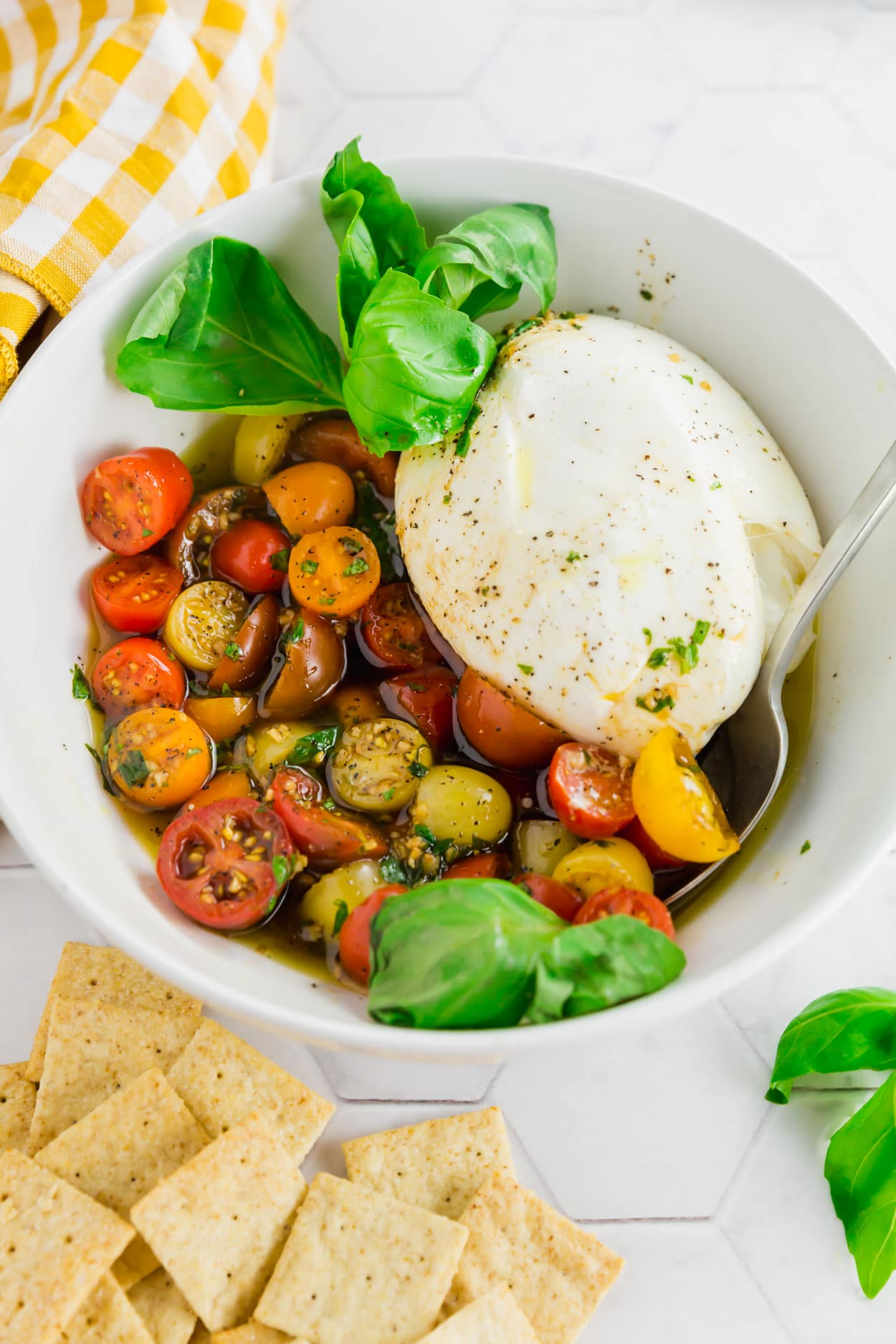 An overhead photo of a serving bowl with marinated cherry tomatoes, burrata and fresh basil with a serving spoon.