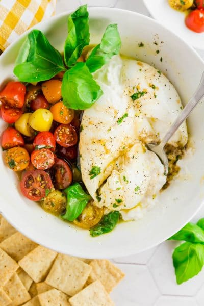 An overhead photo of marinated cherry tomatoes, fresh basil, and burrata in a bowl with a drizzle of olive oil.