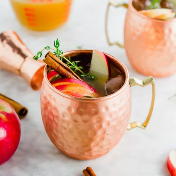 A copper mug filled with apple cider thyme moscow mule with a cinamon stick and apples on top.