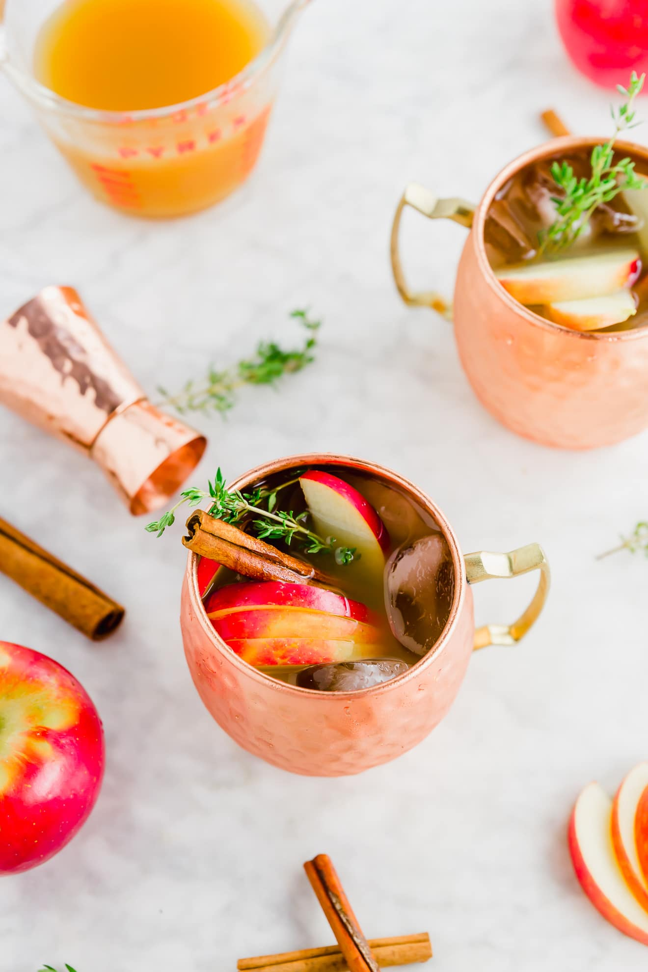 two copper mugs on a marble table filled with apple cider cocktail with a rose gold cocktail jigger and pink lady apples surrounding it.