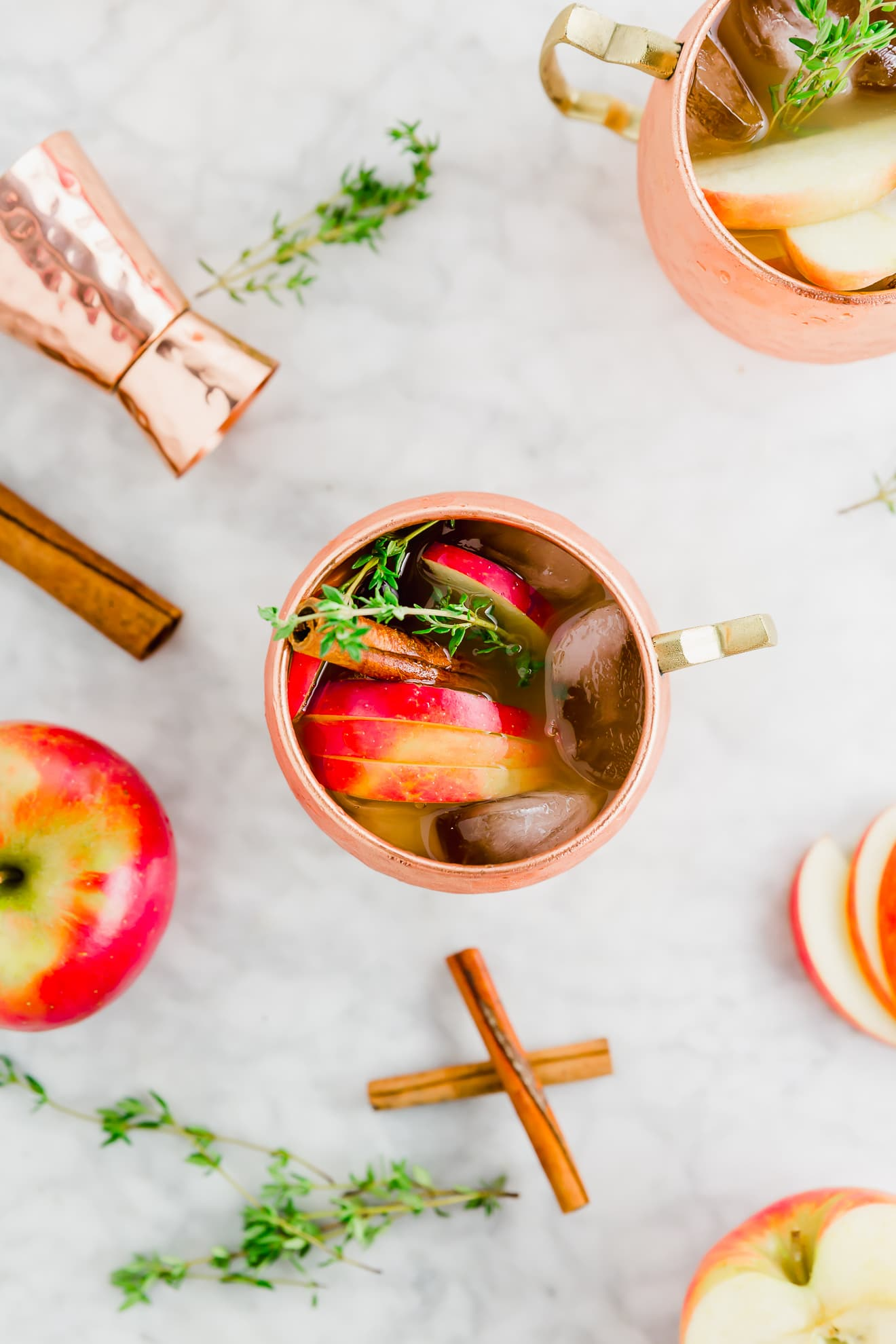 an aerial photo of two glasses of apple cider moscow mule topped with fresh thyme, sliced honeycrisp apples and cinnamon sticks.