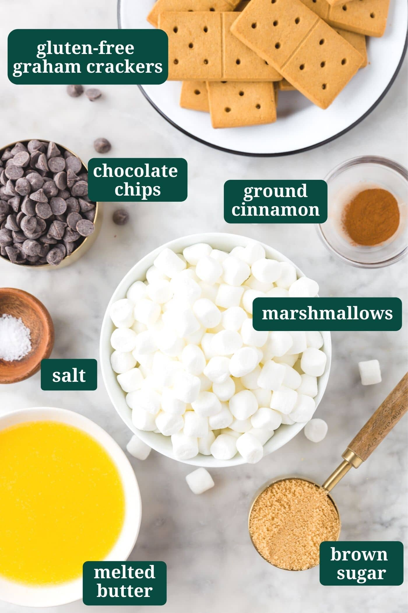 An overhead photo of ingredients for s'mores bars: gluten-free graham crackers, semi-sweet chocolate chips, mini marshmallows, ground cinnamon, salt, melted butter and brown sugar.