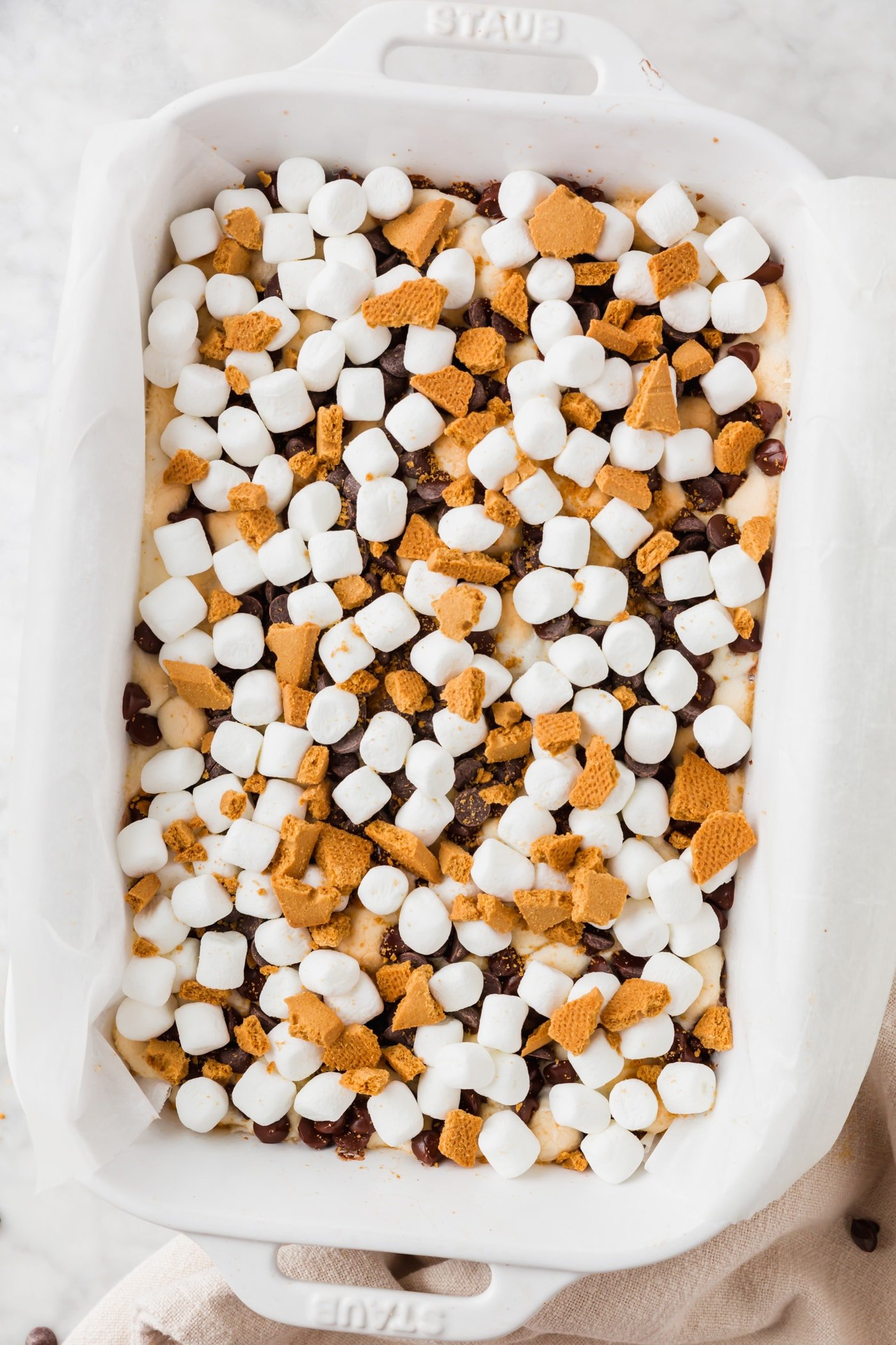 A baking dish with mini marshmallows, graham crackers, and chocolate chips added on top of s'mores bars.