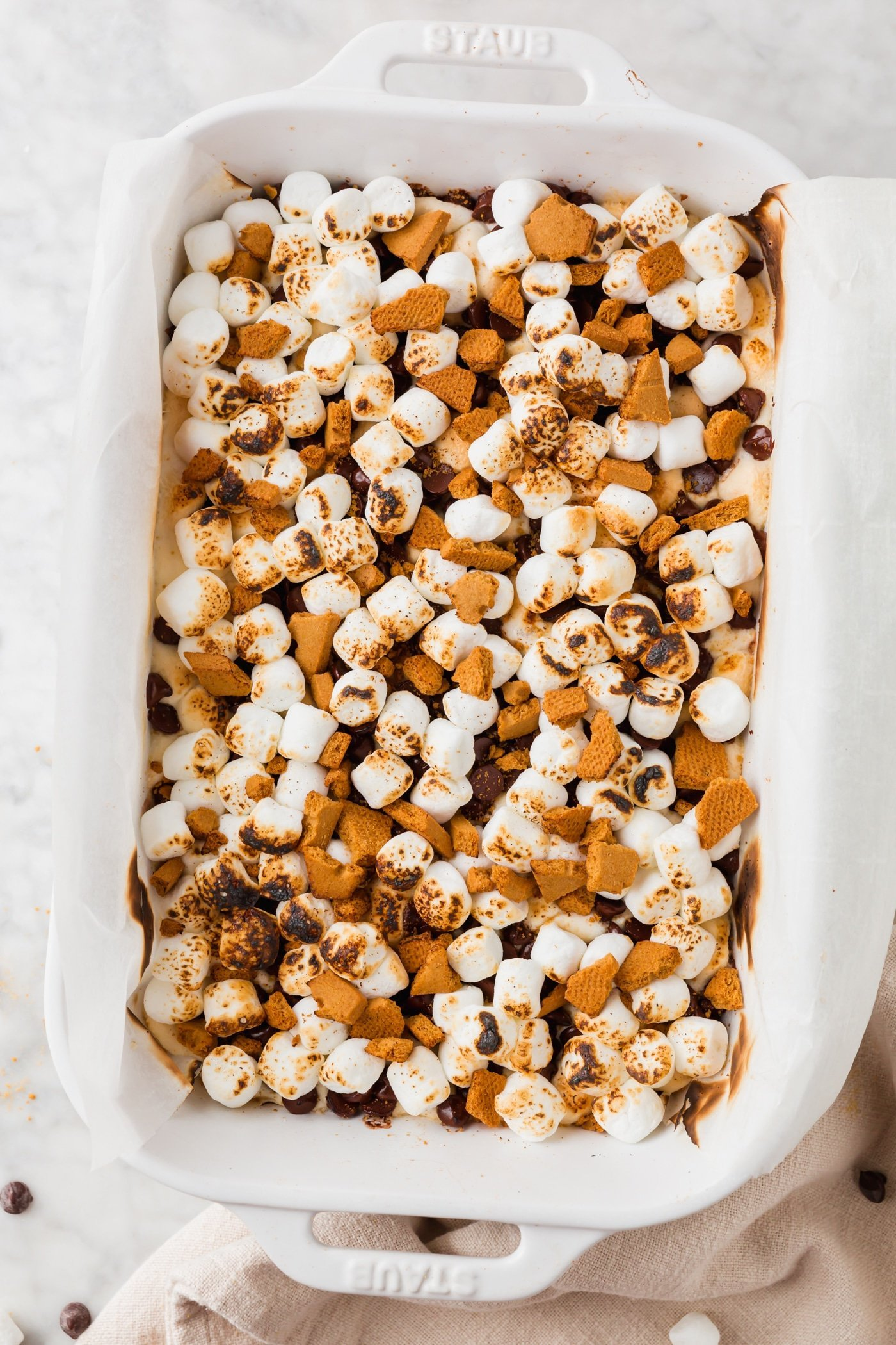 A baking dish filled with s'mores bars that have been toasted with a kitchen torch.