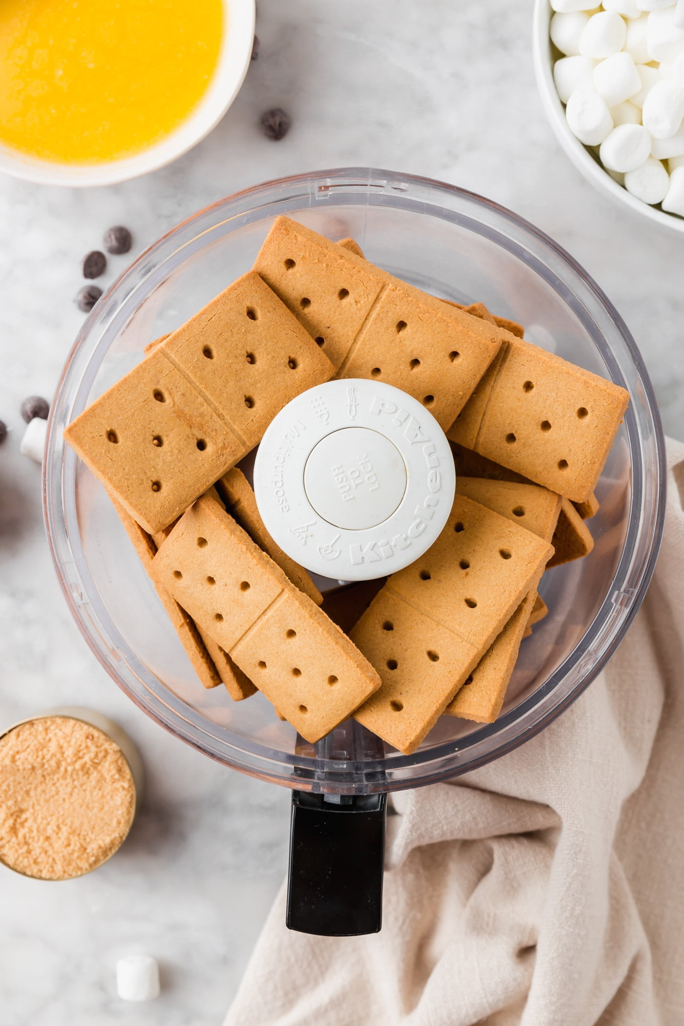 A food processor with gluten-free graham crackers in it.