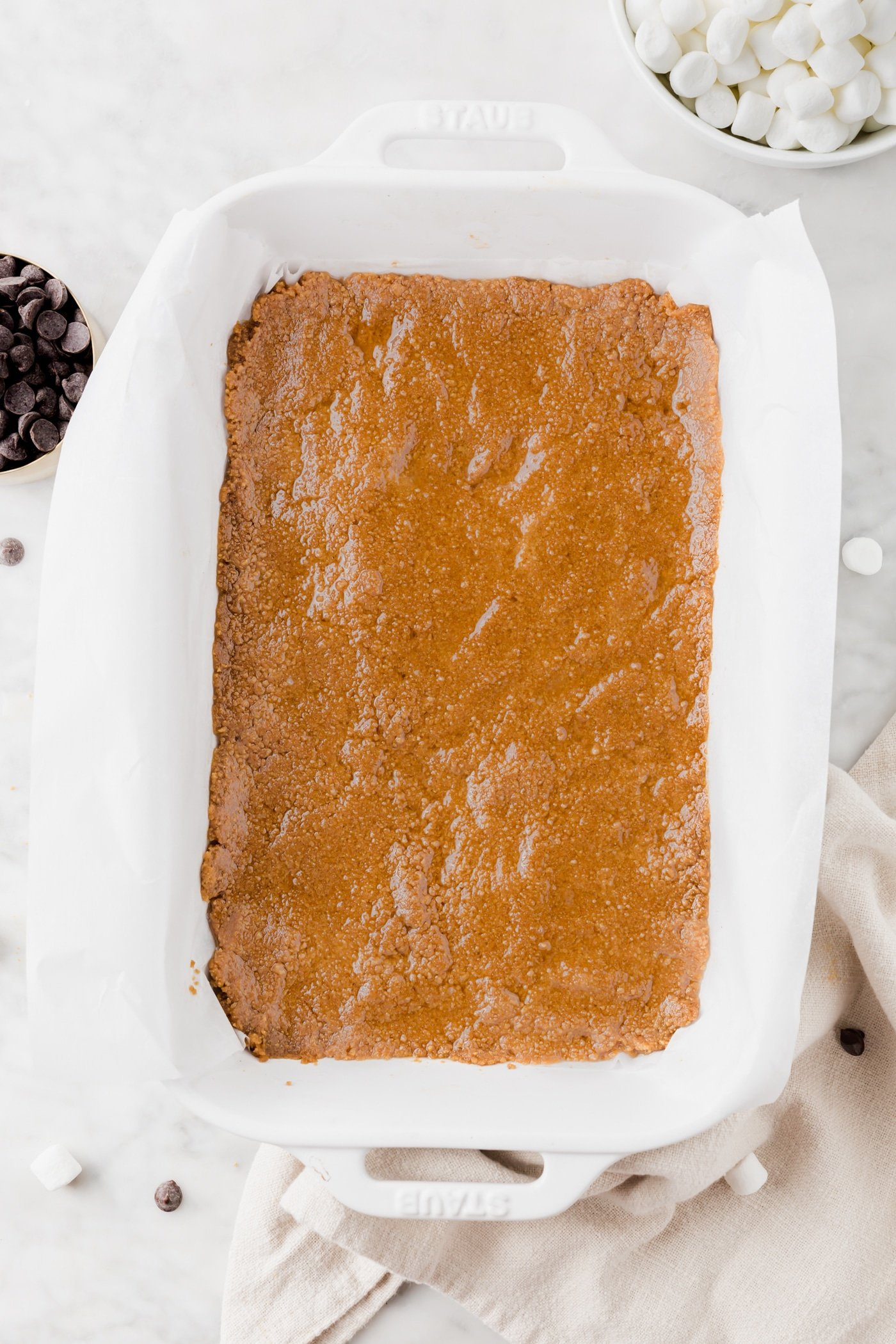 Gluten-free graham cracker crust pressed into the bottom of a baking dish lined with parchment paper.