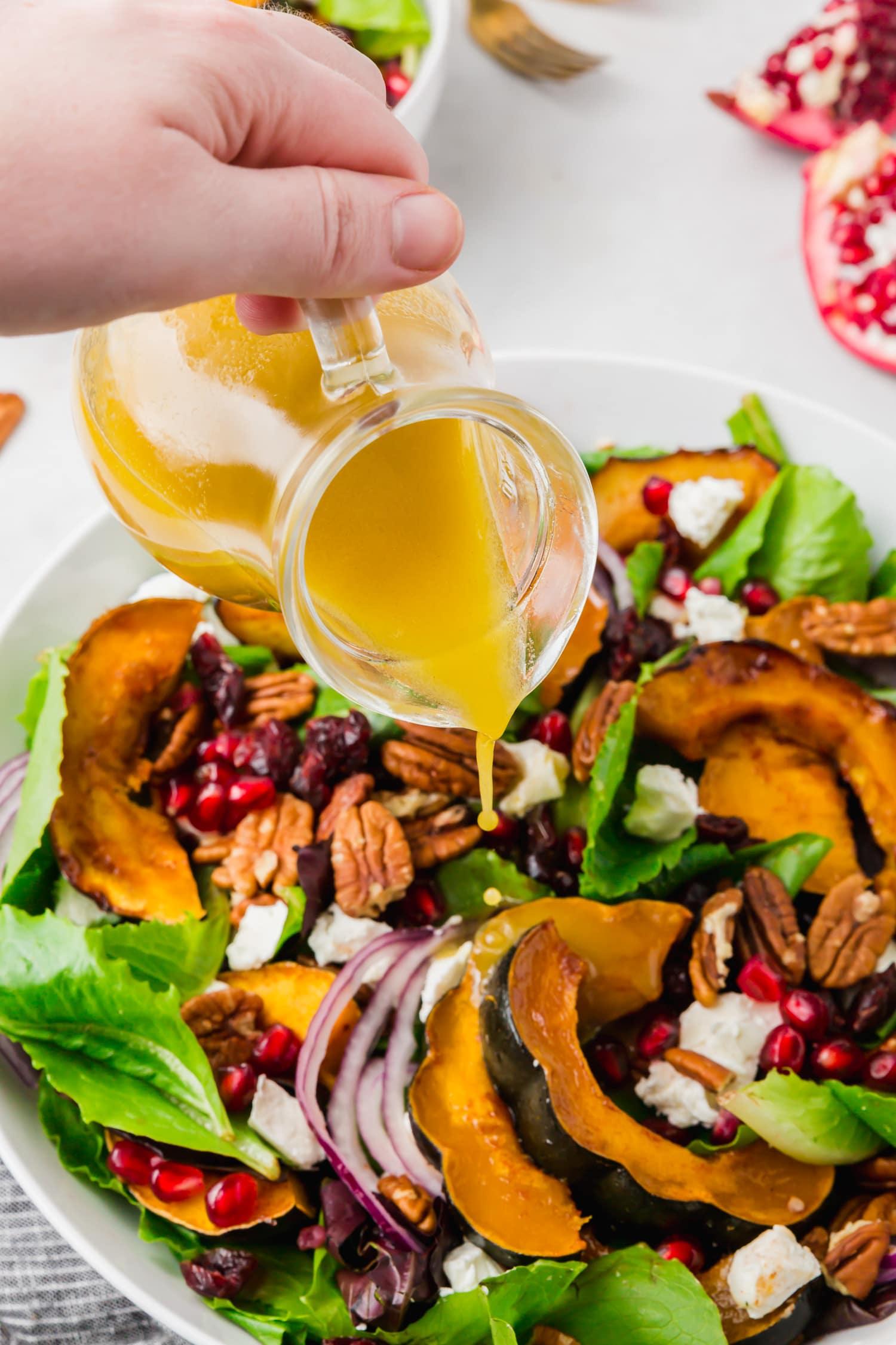 Apple cider vinaigrette being poured on acorn squash salad.