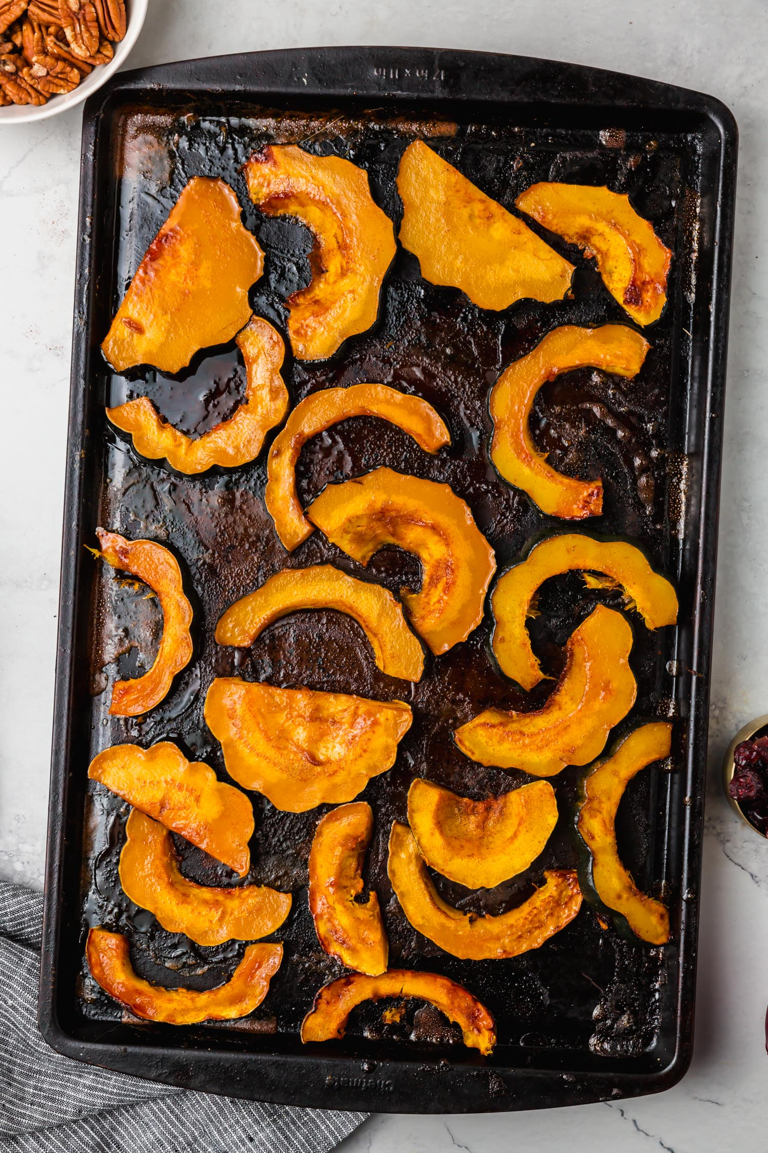 Maple roasted acorn squash on a sheet pan.