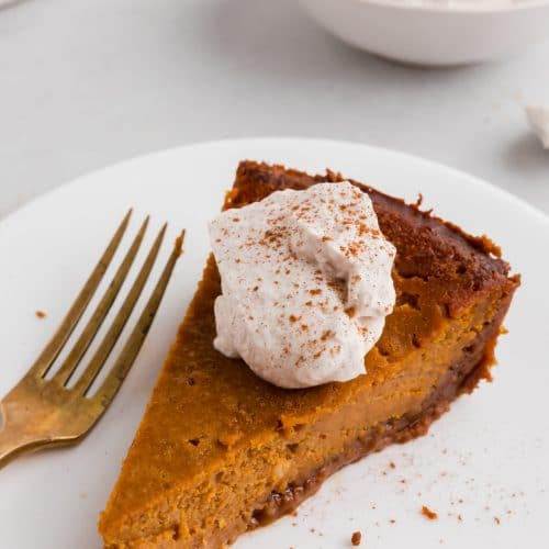 A photo of a slice of pumpkin pie with gluten-free graham cracker crust with a dollop of whipped cream and sprinkle of cinnamon on it.