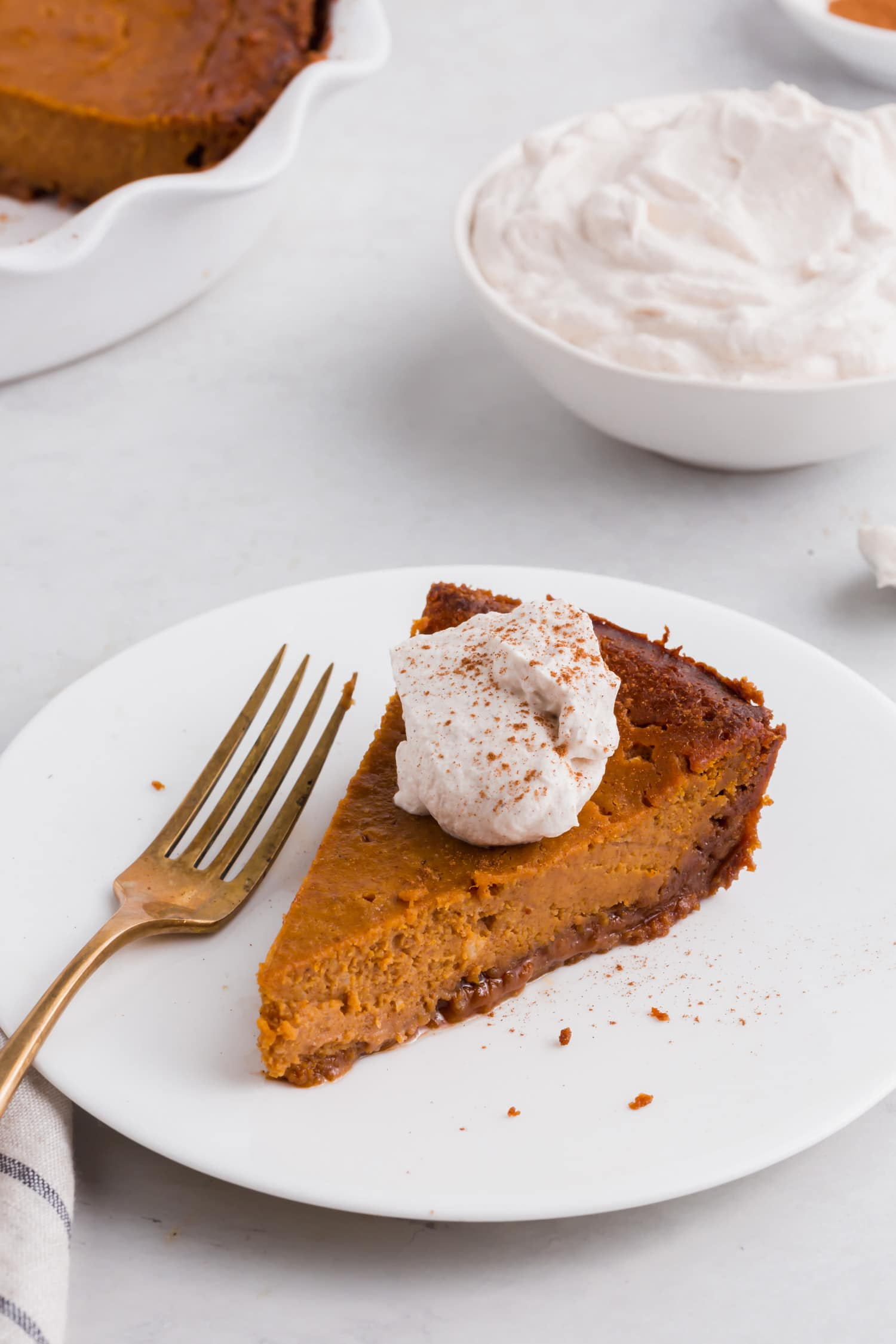 A photo of a piece of gluten-free pumpkin pie on a plate with a fork and a bowl of whipped cream in the background.