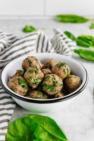A white bowl of baked turkey spinach meatballs with a striped napkin and fresh spinach on the table.
