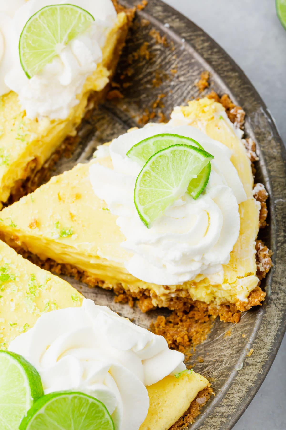 A photo of slices of key lime pie in a pie tin.