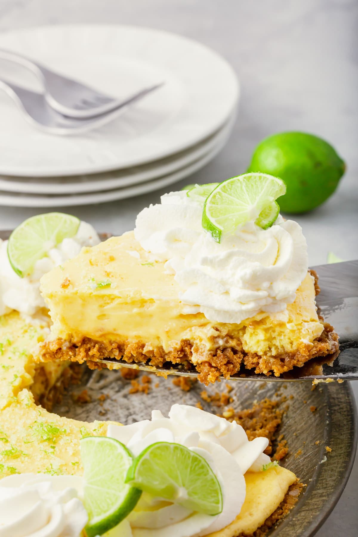 A piece of key lime pie with graham cracker crust being lifted out of a pie tin with a spatula.
