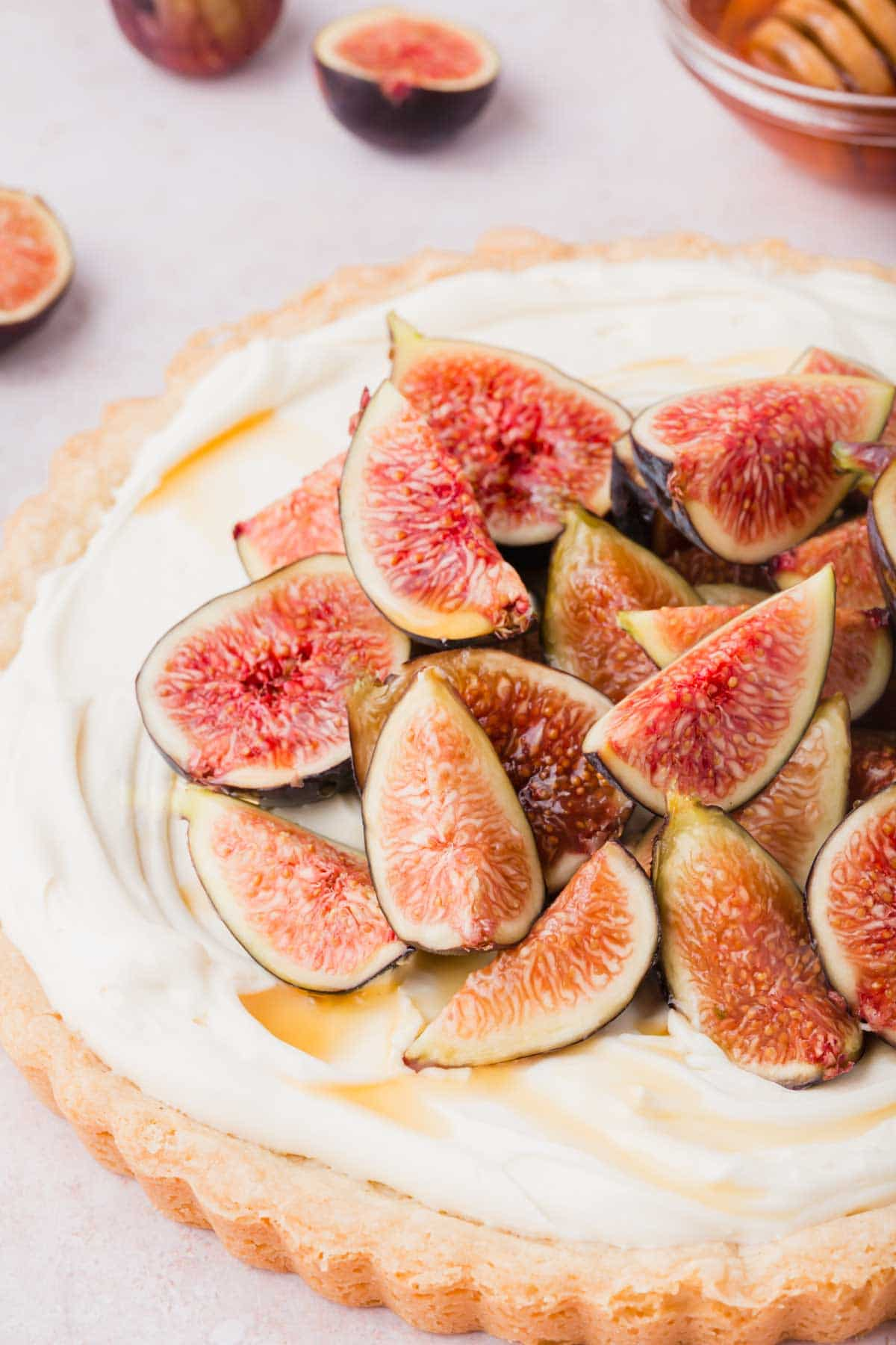 Full tart with buttery shortbread crust, mascarpone filling, topped with fresh figs.
