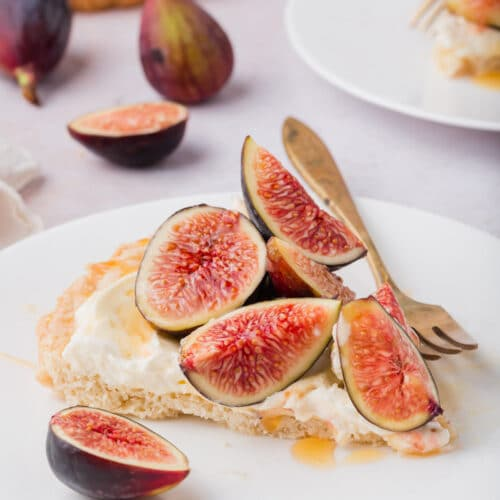 Slice of tart on a plate with fresh figs on top and a drizzle of honey.