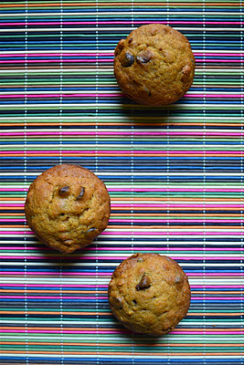 Three pumpkin chocolate chip muffins on a colorful bamboo placemat.