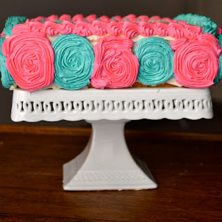 A vanilla cake decorated with pink and blue buttercream decorations on a cake stand.