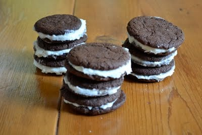 Stacks of homemade gluten-free oreos on a wooden table.