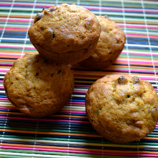 Four pumpkin chocolate chip oat muffins on a colorful placemat.