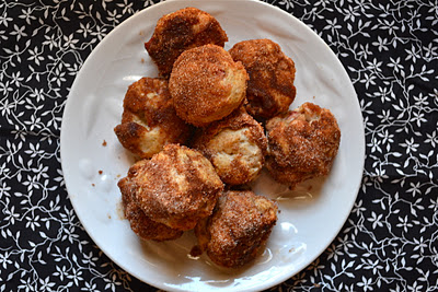 A plate of apple cider donut holes on a black and white tablecloth.