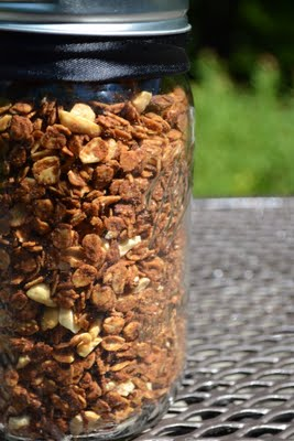 a mason jar of peanut butter granola with a black ribbon tied around it.