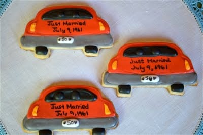 Car shaped anniversary themed sugar cookies on a table.