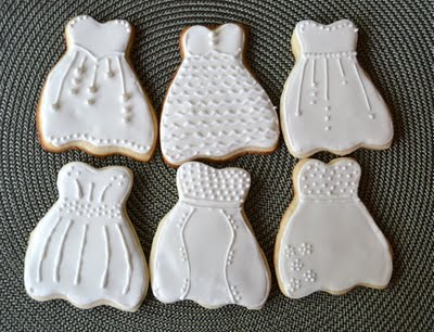 Six wedding dress sugar cookies on a placemat.