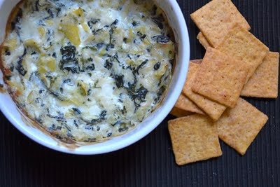 A bowl of hot spinach artichoke dip with crackers on the side.