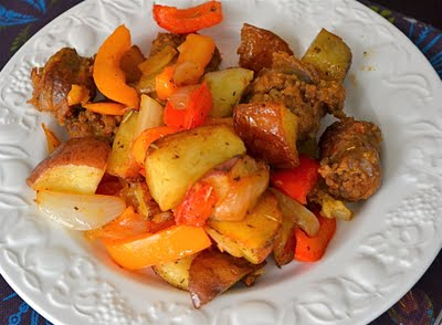 Sausage, peppers and potatoes on a white plate.