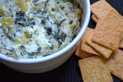 A bowl of spinach artichoke dip with crackers on the side.