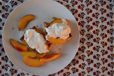 Peach shortcakes topped with whipped cream on a plate with a floral table cloth.
