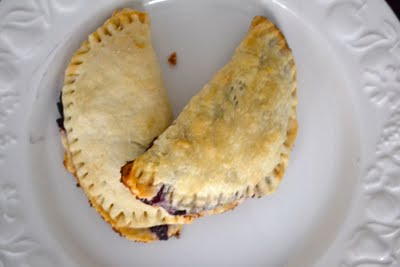 An overhead view of blueberry hand pies on a white plate.
