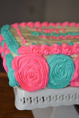 A vanilla cake with pink and blue buttercream decorations.