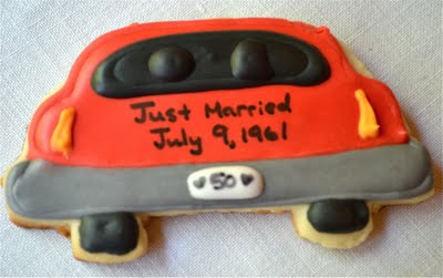 Car shaped anniversary themed sugar cookie on a white table cloth.