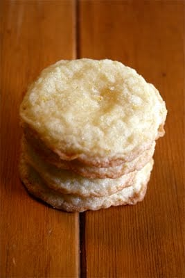 A stack of lemon almond cookies on a wood table.