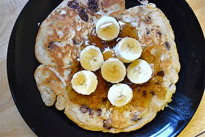 A chocolate chip pancake topped with bananas and maple syrup on a black plate.