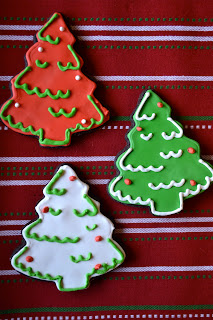 Three Christmas tree sugar cookies decorated in red, white and green royal icing.