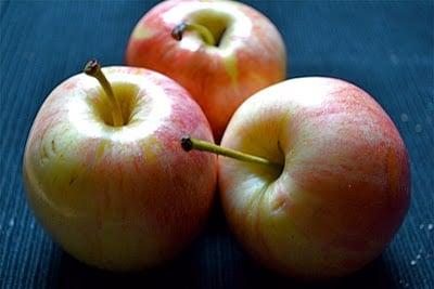 Three apples on a black tablecloth.
