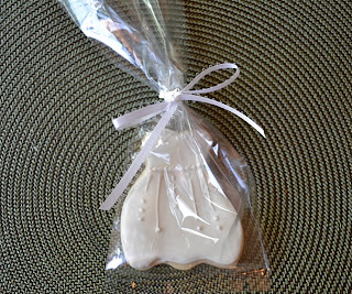A wedding dress sugar cookie in a plastic bag tied with a bow.