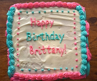 A vanilla cake with blue and pink buttercream decorations.