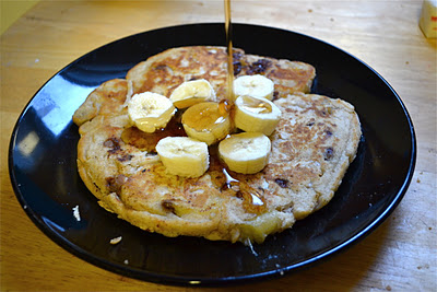 A chocolate chip pancake topped with sliced bananas and maple syrup.