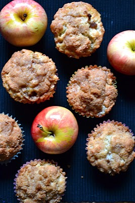 Cinnamon muffins with crumb topping on a table with honeycrisp apples.